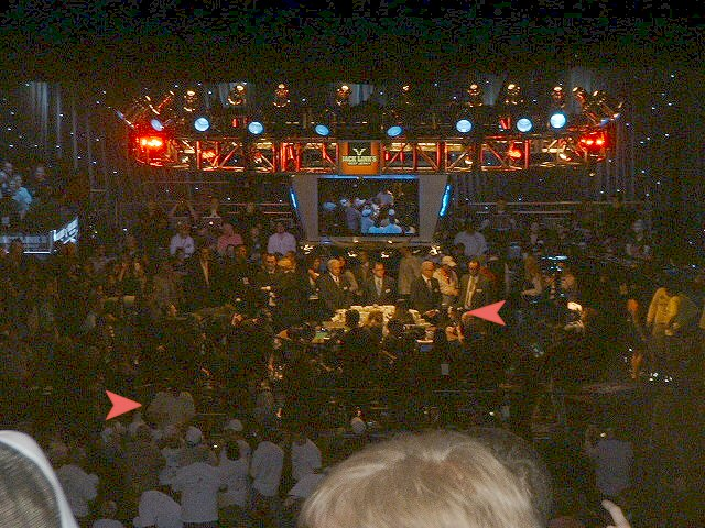 2009 WSOP Final Table Stage with money on the table. Arrow on left points to Darvin Moon signing autographs and arrow on the right points to Joe Cada checking out something on the table.
