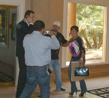 11/07/09 10:54am - Daniel Negreanu poses with a fan while the hotel escort is preoccupied on the phone